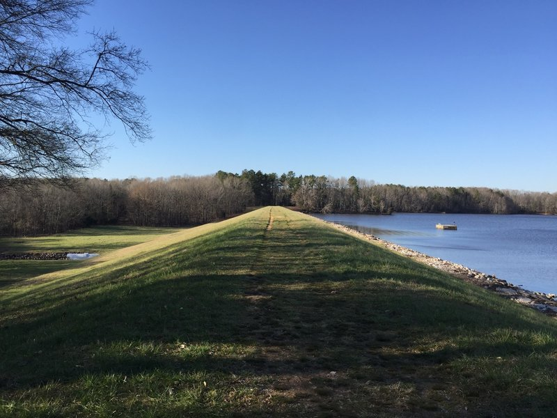 A scenic trail along the top of the earthen dam.