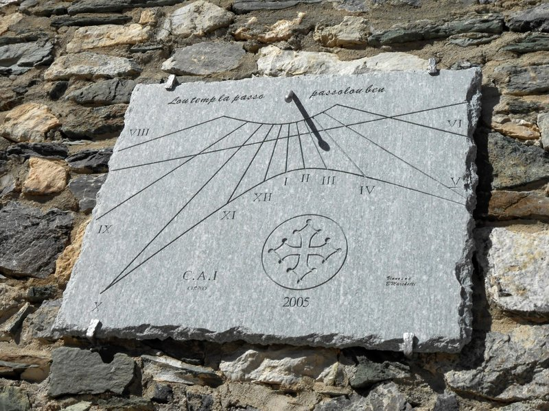 "Sun dial at Rifugio Gardetta. In Occitan language, it reads ""Time goes by. Pass it well."""