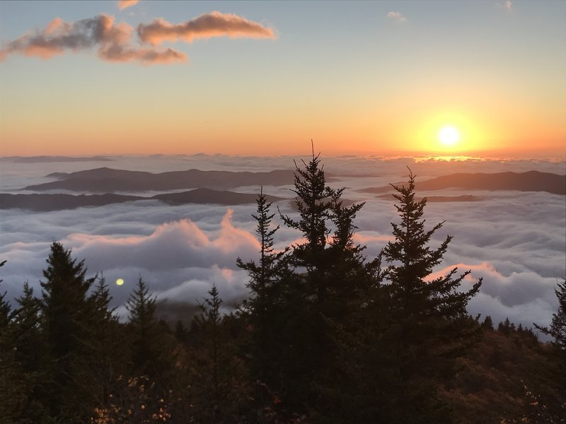 Sun rising over the cloud encased South Toe River Valley as the wind begins to whip up the just moments before still clouds as seen from Sunrise Point along the Woody Ridge Trail
