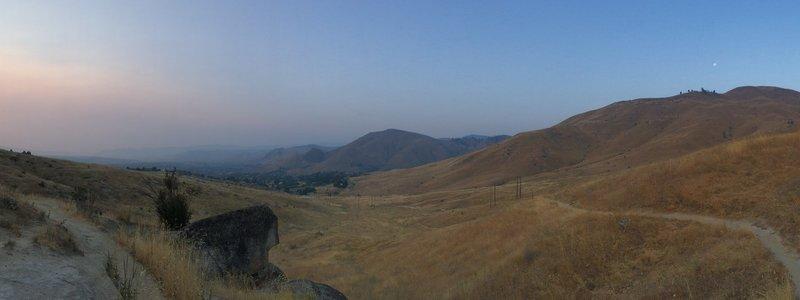 Smokey sunrise opposite the moon with Wenatchee Valley in between.