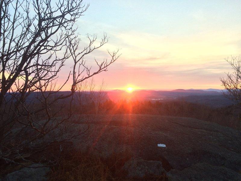 The rising sun as it burns above the blaze.