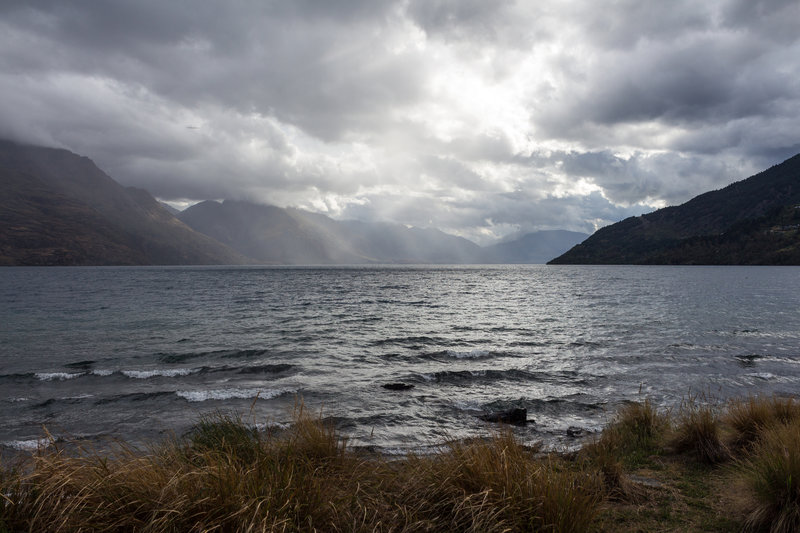 The sun breaking through the clouds on the rainy day looking across Lake Wakatipu