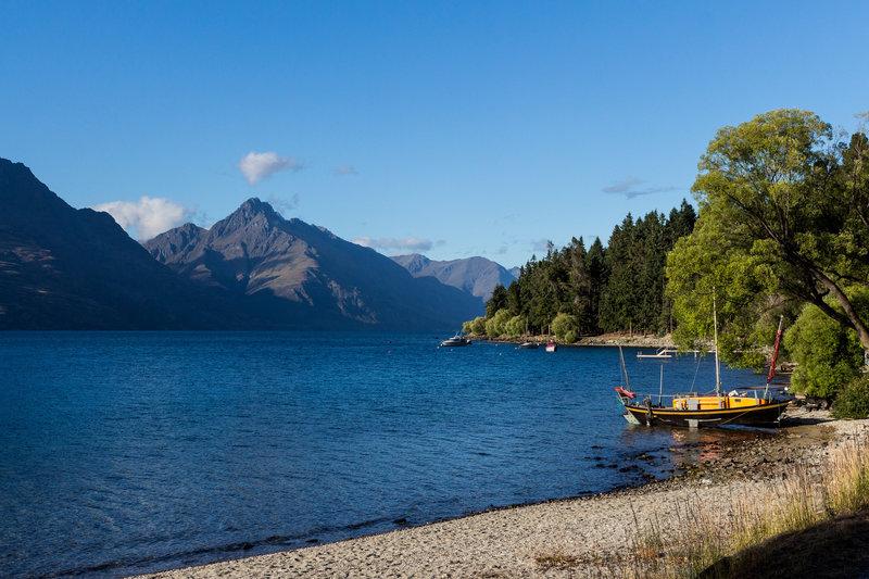 Small boats are anchored at the shore of Lake Wakatipu