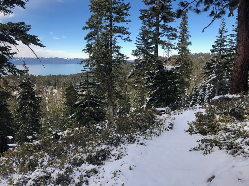 View of the lake with a few inches of snow on the trail
