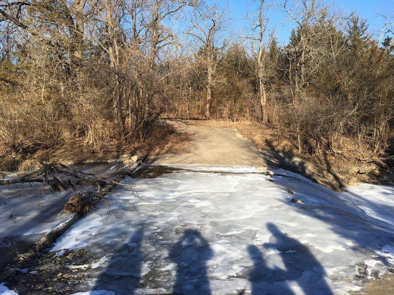 A frozen, paved creek crossing.
