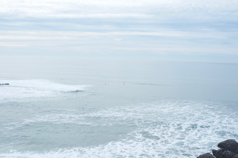 Surfers wait for waves in the ocean below.
