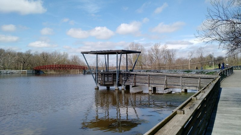 One of the two fishing piers on the flat side of the lake with the bridge over the spillway in the background.