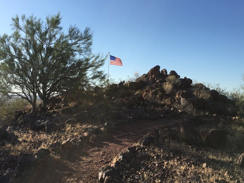 The trail continues past the flag to make its way to the summit.