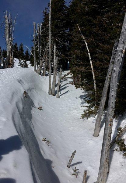A deep snow crevasse off the path.