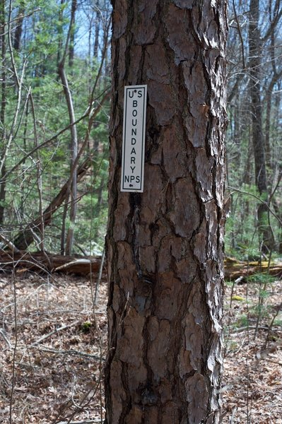 The park boundary is marked by a simple sign on a tree next to the trail. The trail continues on for a short distance to the road.