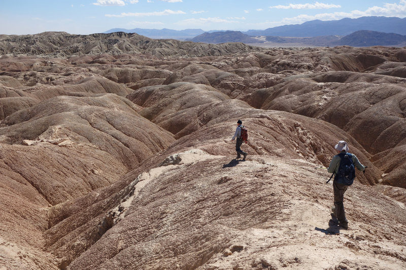 Two hikers descend into the badlands near Font's Point.