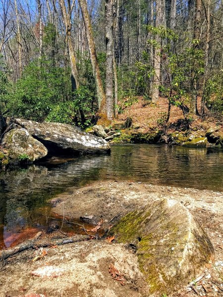 A hand-chiseled millstone lies abandoned in the creek