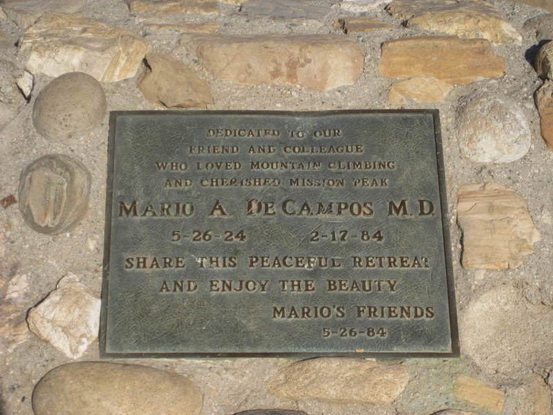 """Monument at the top: """"Dedicated to our / friend and colleague / who loved mountain climbing / and cherished Mission Peak / MARIO A DE CAMPOS MD / 5-26-24   2-17-84 / Share this peaceful retreat / and enjoy the beauty / Mario's friends / 5-26-84"""