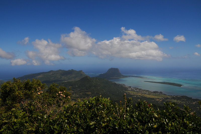 Excellent views south from the summit. The prominent rock surrounded by reefs is Le Morne Brabant, and UNESCO site with a tragic history.