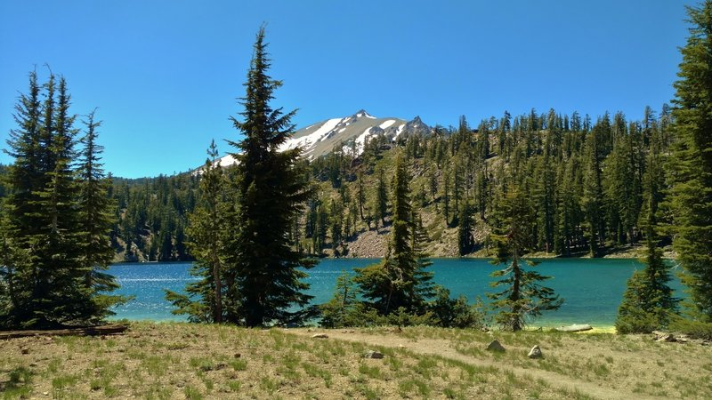 Lassen Peak is seen to the west, across Shadow Lake, as Terrace, Shadow, and Cliff Lakes Trail runs along the shoreline.