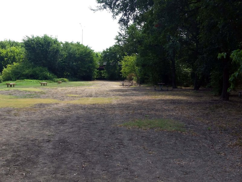 Benches to the left by the pond, and picnic tables to the right, on the trail leg shared by Pond & River Loops