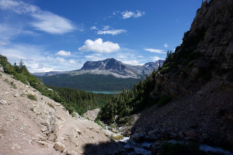 Lake Sherburne and Wynn Mountain can be seen across the valley from the waterfall.