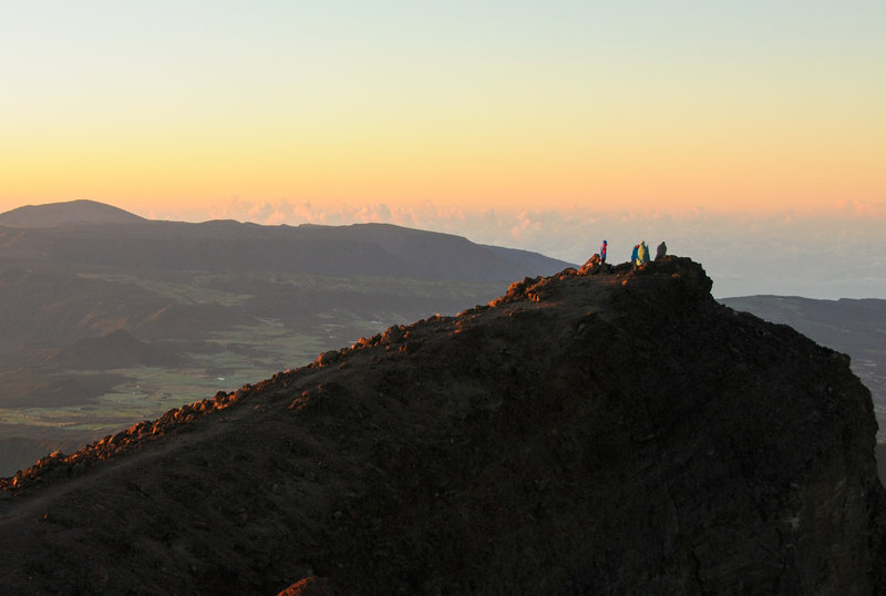 Some hikers enjoy sunrise on Piton des Neiges' sub-peak with Piton de la Fournaise in the far distance.