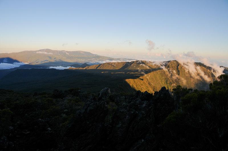 Clouds climb out of Cirque de Cilaos at dusk. Piton de la Fournaise is in the distance.