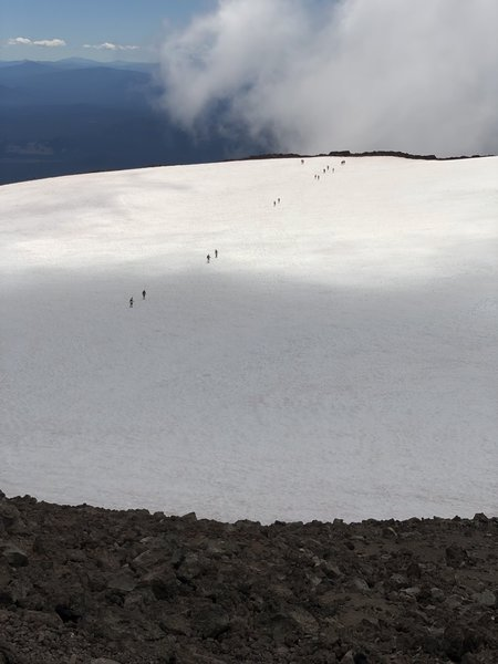 Hikers crossing the crater snowfield