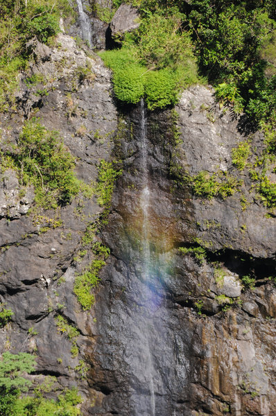 A small waterfall plunges towards Bras Bemale while creating a small rainbow