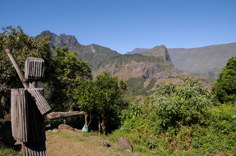 A wooden statue of a hiker can be found near a picnic table at the southern base of Piton Cabris. In the distance is Grand Benare.