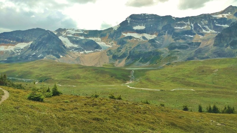Mountains, snowfields, glaciers, and a small lake rise above the Jonas Creek valley at the creek's headwaters. Seen just below Jonas Shoulder when looking west.