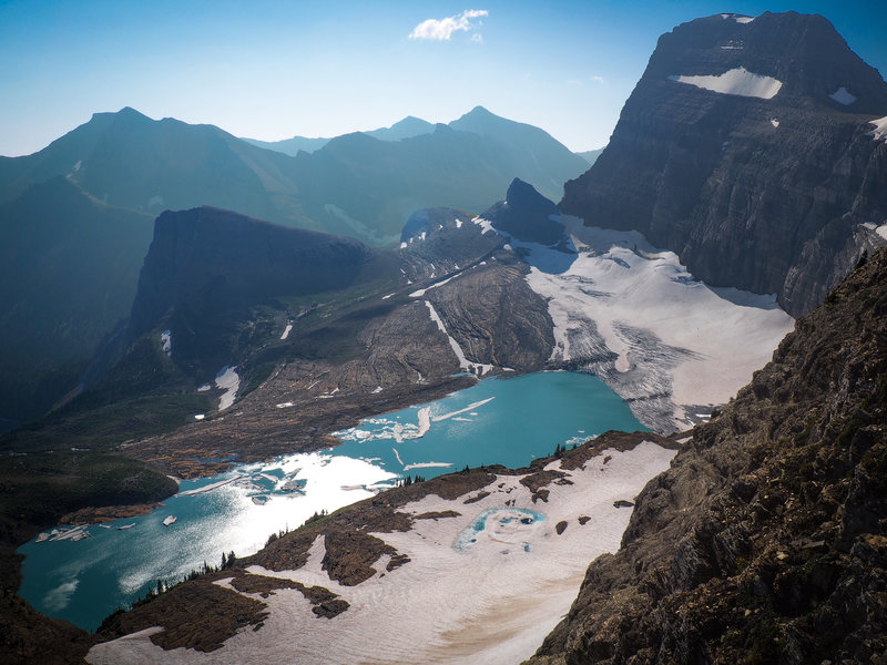 Atop the Glacier Overlook, Upper Grinnell Lake and Grinnell Glacier stand out as the dominant features. Angel Wing (left-center), Mount Gould (top-right), and Salamander Glacier (bottom) also appear.