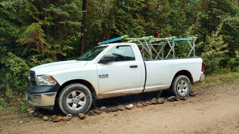 Parked truck wrapped with chicken wire to prevent porcupines from eating brake lines, etc.