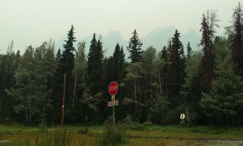 Yellowhead Mountain with its many peaks, on a hazy, overcast morning, as seen from the trailhead. The trail sign is at the very left, behind the railroad tracks.