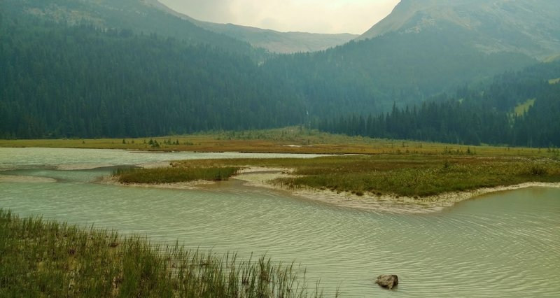 A small glacial lake in the mountain meadows, is passed by Coleman Glacier Trail. This lake is fed by the glacial creek flowing down the gap in the center between the 2 mountains. A glacier behind the mountain on the right is the creek source.