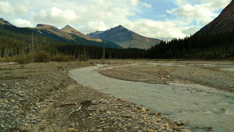 The Smoky River spread out across gravel flats, making for a lower water level and easier ford. Tatei Ridge is the mountain in the center with Chetang Ridge to its left. Seen looking upstream (southeast) at the alternate Smoky River crossing.