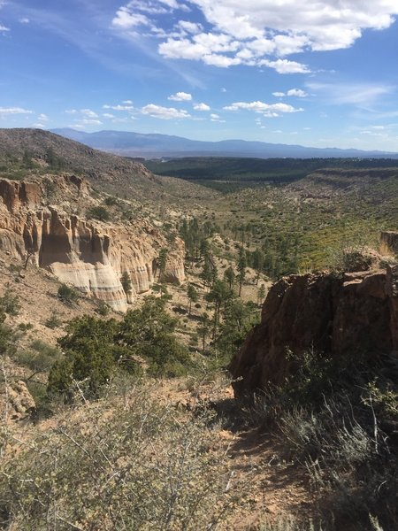 Cliffs with Sangre De Cristo Mountains in the distance.