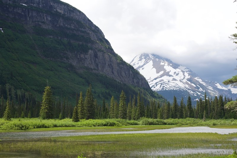 Mirror Pond sits at the foot of the Citadel Mountain. Blackfoot Mountain sits in the background, home to Blackfoot Glacier.