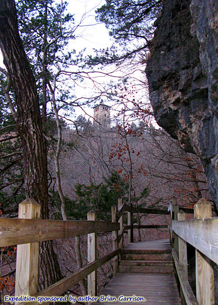 """On the Spring Trail, where the upper boardwalk skirts around a cliff face. Without leaves in winter, it's easier to see distant features, such as the """"castle's"""" water tower in the background.  About:  37.973922, -92.766711"""