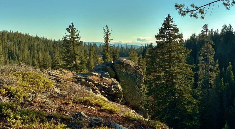 Fir forested hills stretch into the far distance when looking southeast from a rocky bluff in a remote area near the southern border of Lassen Volcanic National Park, along Twin Meadows Trail.