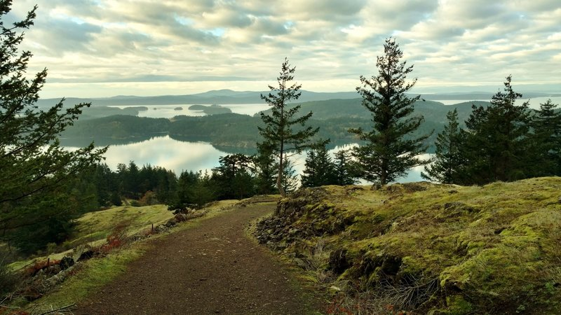 San Juan Islands and the southern tip of Vancouver Island in the far distance, looking south-southwest when approaching the West Overlook on South Trail.