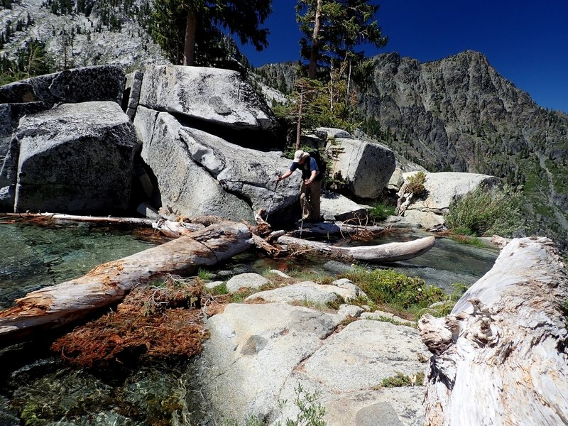 Crossing the outlet of Grizzly Lake, 20 feet from a 200-foot cliff