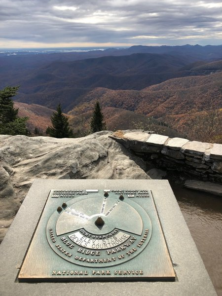 Summit plaque with directions of mountains in the distance.