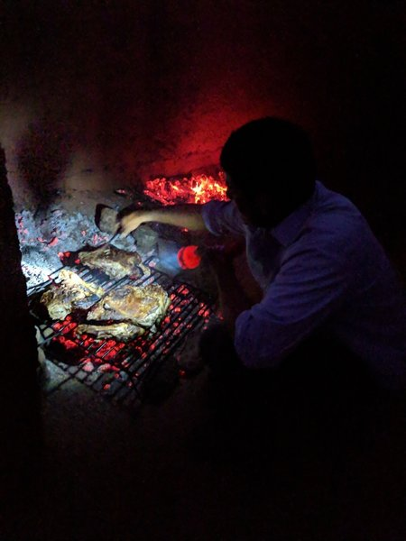 Cooking the cordero pieces over the fire.