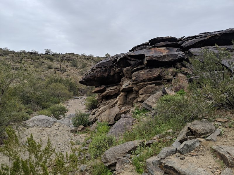 On the back side of this formation, the wash has carved a shallow cave into the rock. You'll see it coming down from the JC trail peak.