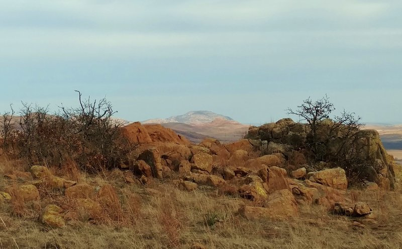 Mt. Scott in the distance, rises above nearby hills in the Wichita Mountains Wildlife Refuge. Seen looking east-northeast from high on Elk Mountain Trail.