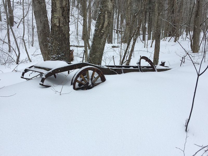Old farm equipment or old car with wooden wheel spokes.