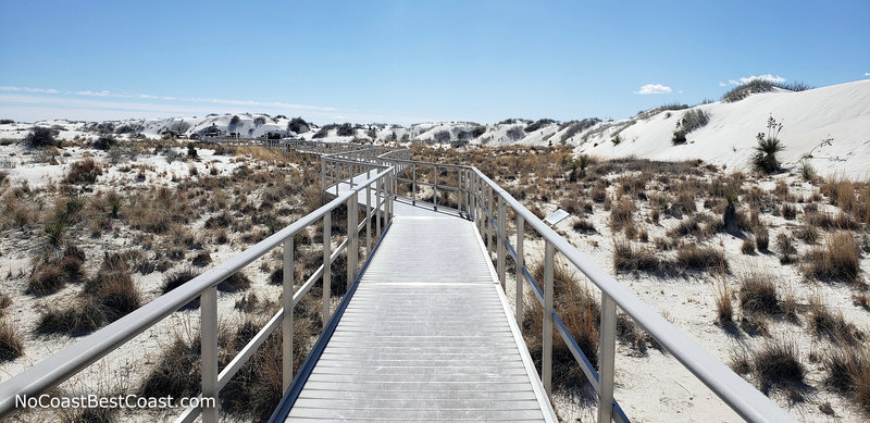 The wheelchair accessible Interdune Boardwalk surrounded by mounds of white gypsum sand.