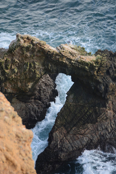 Watch the waves break through a rock arch formation at the end of Chimney Rock trail.