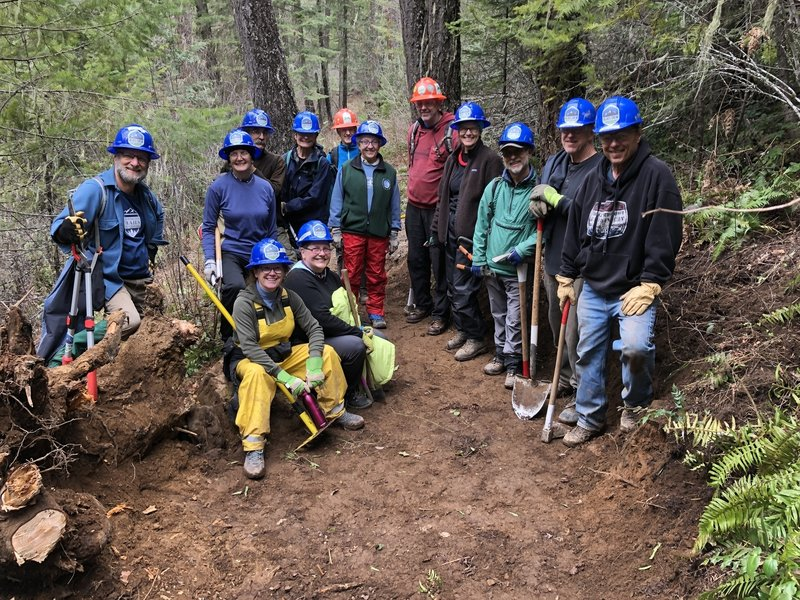 Blues Crew celebrating the repair of a large root ball hole in the trail.