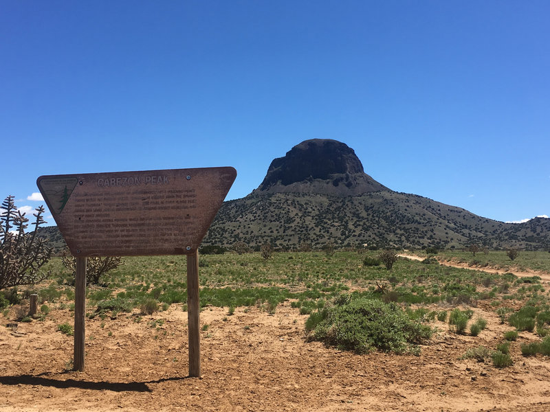 Cabezon Peak looms in the background as the BLM sign in the foreground marks the turnoff to the unpaved road leading to the parking area at the trailhead.