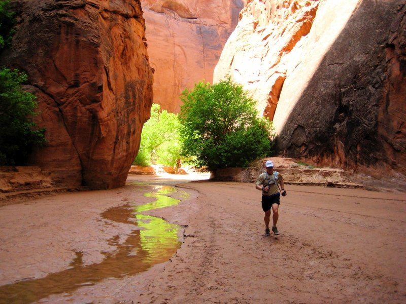 "Chris runs past the large, open ""chamber"" near the end of Buckskin Gulch. There is a campsite here, but reservations are required years in advance."