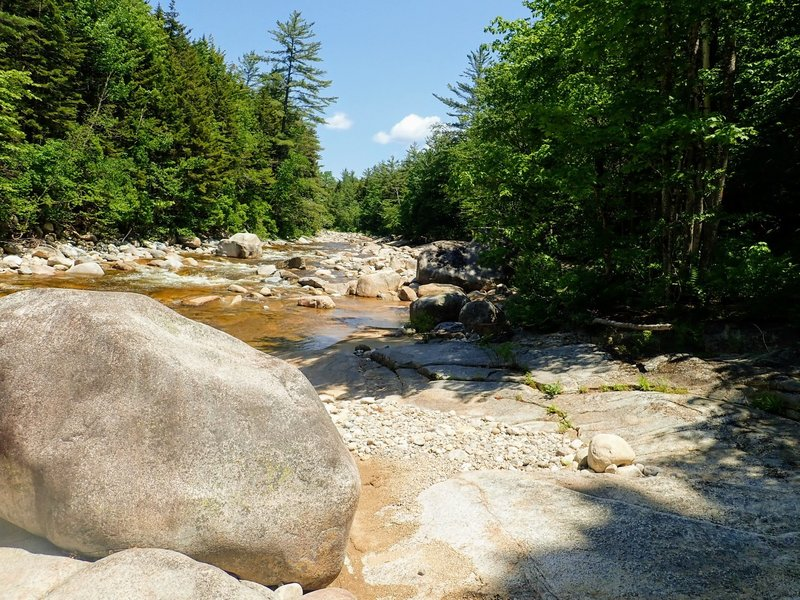 The trail juts out into the river on a large rock (looking upstream).