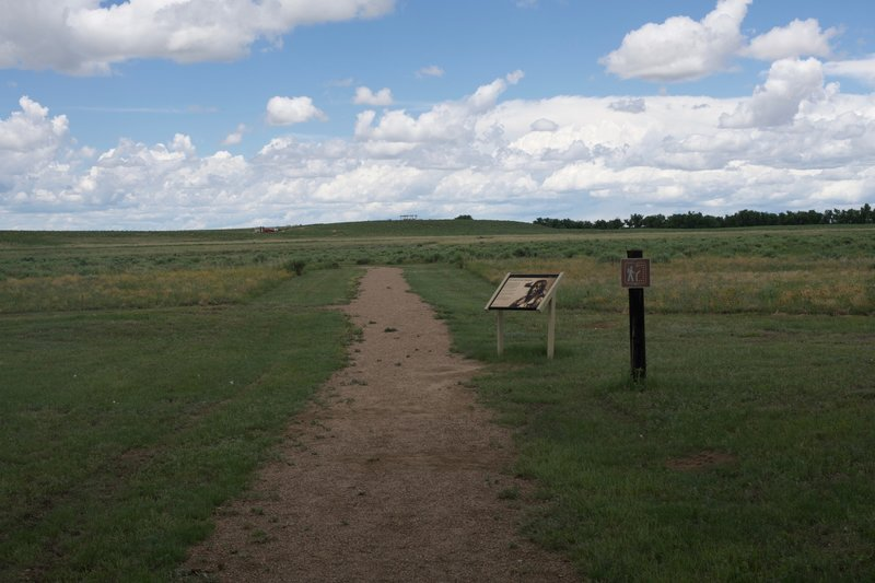 The trail departs the picnic area and heads toward the monument on the hill, roughly 0.5 miles away.